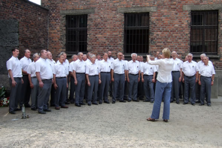 The choir perform a poignant item in the yard of Block 11, a notorious hospital and punishment block in memory of those who perished in this place.