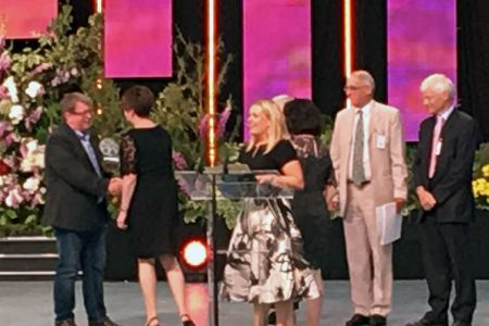 61.Dave Jones (Chairman) presenting the Male Voice Trophy to Nia Clwyd, MD of Bois y Castell at the Llangollen International Musical Eisteddfod. The Fron Choir have sponsored the Male Voice Choir Competition Trophy since 1971 in memory of our Founder Cond