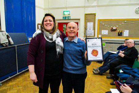 01C. Ron Wilkinson receives his ten year service award from Leigh Mason choir Musical Director 31/01/2019