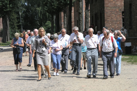 Auschwitz tour with a guide. To minimise disturbing the atmosphere of the concentration camp the guides  speak very quietly into lapel microphones and are heard by the members of their group through headphones.