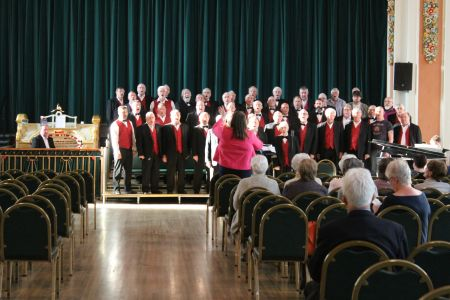 08A. The choir warm up in Stockport Town Hall Ballroom whilst our guest Nigel Ogden watches on from the seat of the Wurlitzer organ